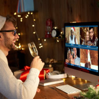 Happy man wears santa hat celebrating New Year party with friends on video call.